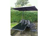 Large glass patio table, parasol, and six chairs.