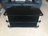 Black glass TV stand, 3 tiers offering 2 shelves. 4 sturdy legs with metal frame