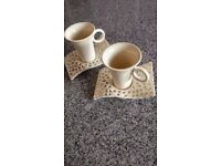 A pair of unusual cream coffee cups and wave saucers.