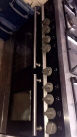 A 5 Burner cooker, Gas, With Two Ovens. Black and Silver