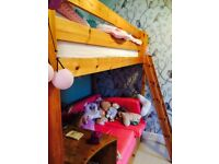 Children's wooden high bed with pink cushion sofa and desk underneath