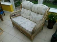 Two seater cane sofa arm chair. Wicker conservatory seat