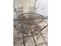 Wrought iron garden/patio table, 4 folding chairs with cushions in good condition
