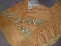 pair of lined heavy gold curtains with pelmet and tie backs