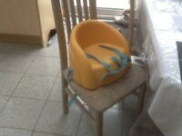 Booster seat with straps and harness to attach to dining chairs for toddler to sit at dinner table