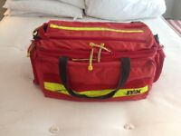A large red paramedic bag and med kit .