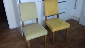 A pair of fabric dining chairs.