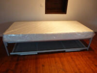 2 grey metal framed single beds with mattresses one folds and lies underneath the other