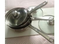 Set of stainless steel saucepans with glass lids