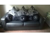 Black leather sofa (new) with matching footstool