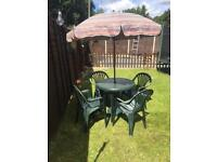 Plastic garden table and chairs with parasol