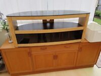 Light wood and glass tv stand with two shelves, bottom shelf has glass doors, excellent condition.