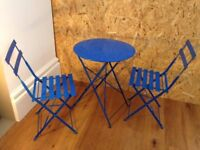 Blue metal bistro table set with two matching chairs.