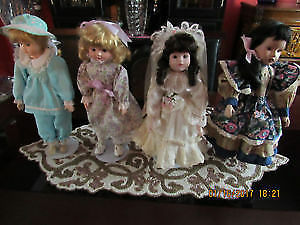 Four antique vintage porcelain dolls on stands