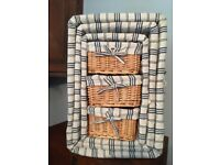 Set of wicker baskets for storage. All baskets are cloth lined and sit together.