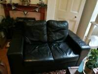 Two seater black faux leather sofa
