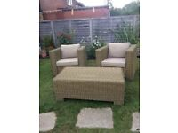 Two wicker garden chairs with cushions and glass topped occasional table