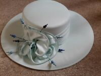 Ladies powder blue hat with pearl decorations and bow at the side.