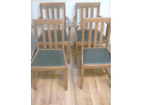 4 x Wooden dining chairs with green padded seats.