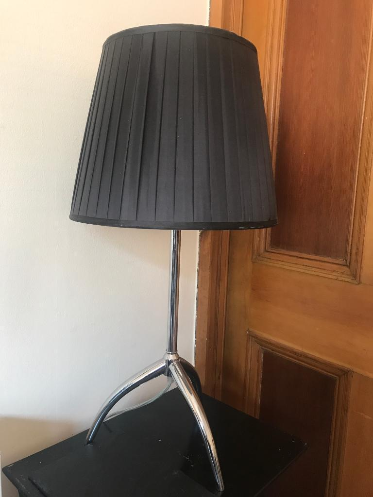 Lamp with silk shade and chrome legs .