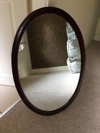 Antique dark wood oval mirror