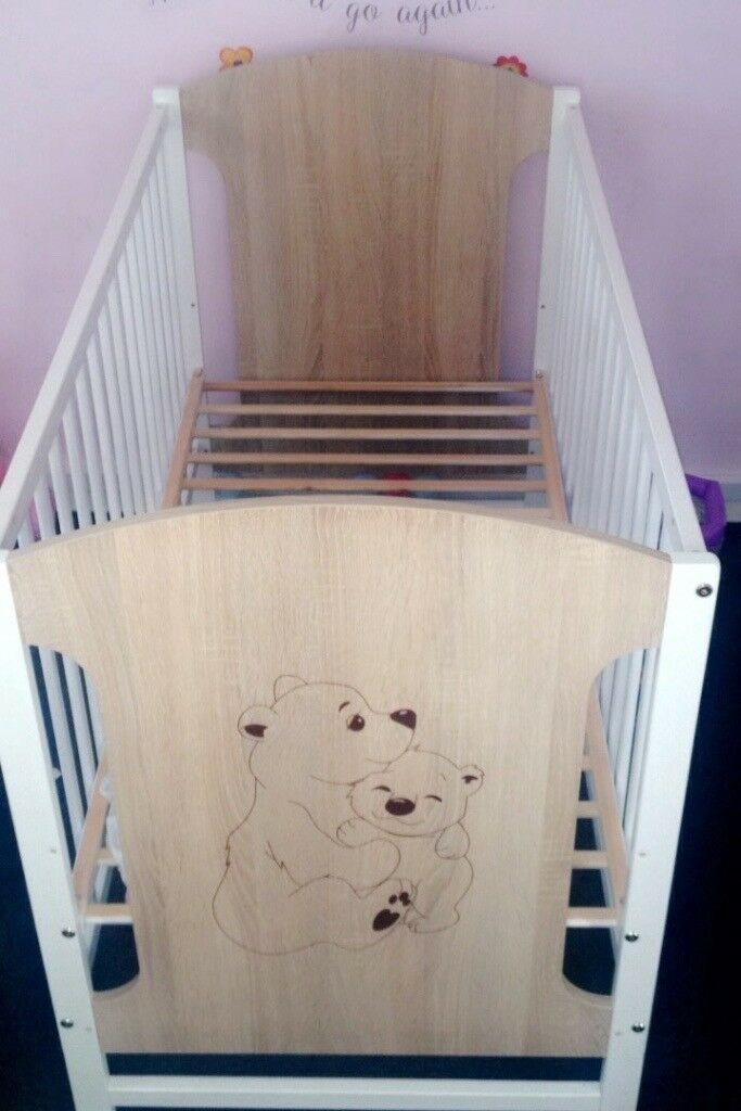 Light brown and white cot with mattress