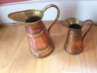 Two old copper watering jugs.