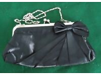 AS NEW BLACK FABRIC CLUTCH BAG. CHAIN HANDLE FOLDS INSIDE.