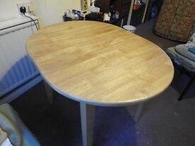 Oval dining table, seats 4-6 people, solid light coloured wood.