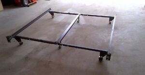Queen bed frame with a center bar, on wheels, adjusts
