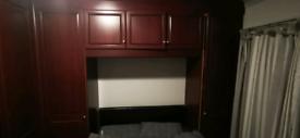 Large L shape solid wood over bed wardrobes