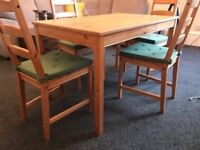 Ikea dinning table with 4 chairs and cushions.