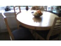 round table in solid wood which is light pine colour with 4 matching chairs with black seats vgc