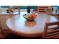 SOLID WOOD round dining table with 4 matching chairs which have black seats vgc