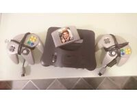 Nintendo 64 with two grey controllers and golden eye