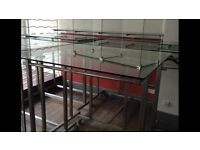 Retail retail clothes hanging rails in stainless steel and shelving all with glass tops.
