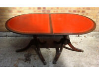 Unusual extending oval dark wood dining table inset with red leather