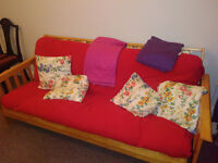 Wooden brown light sofa bed / futon with red IKEA throw