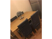 Dining table with four faux leather chairs