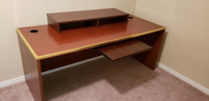 Large office desk with metal trim and monitor stand