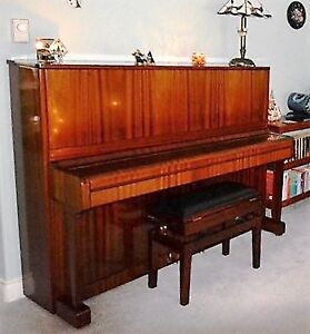 Upright Petrov piano with lovely tone. Includes matching stool.