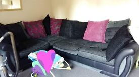 Black and grey corner sofa with square storage pouf and extra scatter cushions