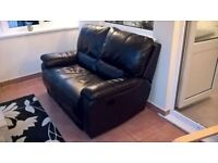 Two-seater black leather sofa with twin recliners. £70 o.n.o.