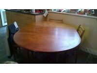Solid wooden round dining table, fold out extendable leaf with four chairs.