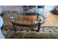 A modern coffee table with an oval shaped glass top, and grey metallic frame.