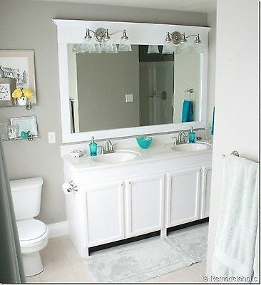 A framed mirror makes a large builder mirror look custom. image:Remodelaholic