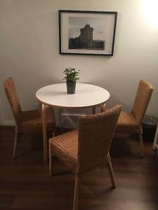 Round dining table and wicker chairs