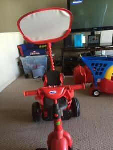 Red Little Tikes bike with push handle and shade canopy