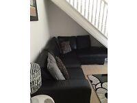 Black leather corner sofa and foot stool