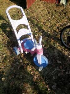 two girls push tricycles
